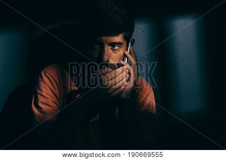 Prisoner Man In Dark Cell Using Cell Phone Discreetly