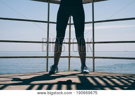 Athletic Female Legs In Blue Sneakers And Sweatpants Against The Sea In The Early Morning