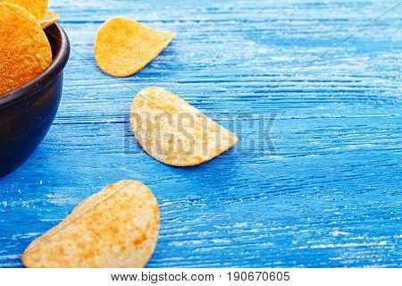potato chips in an earthenware dish plate stands on a wooden background. beer snack unhealthy eating