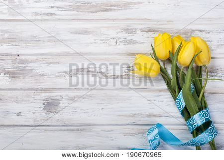 bouquet of yellow tulips and gift box with blue bow on vintage blue wooden table background. holidays concept. Copy space.