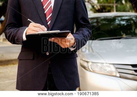 Confident smiling car salesman at the showroom he is standing with arms crossed luxury cars on the background