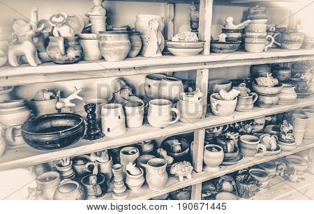 Old vintage photo. Wooden racks in a pottery workshop in which there are pottery, many different pottery standing on the shelves in a potery workshop. Low light