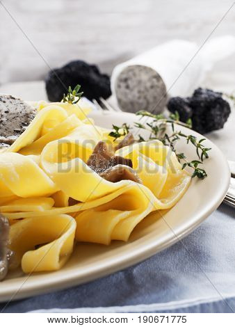 Pappardelle pasta with mushrooms and black truffle butter. Selective focus.