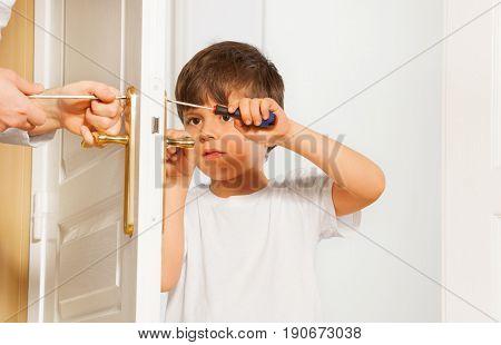 Portrait of kid boy drawing up bolt of door handle using screwdriver