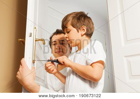 Portrait of young father helping his six years old son to fix door-handle using a screwdriver