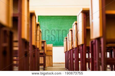 Path between desks leading to green blackboard in a classroom