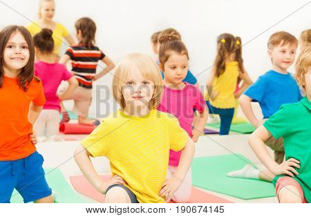Big group of happy kids kneeling with their hands on waist, during gymnastics in sports club