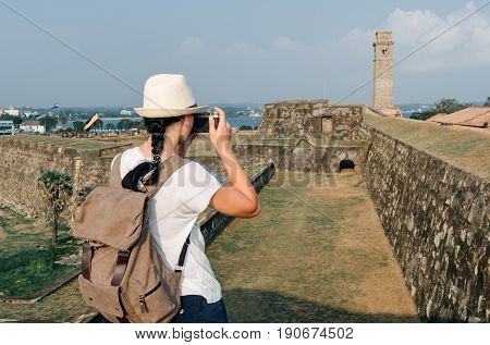 Girl Traveler With A Backpack And Camera. City Clock Tower In The Town Of Galle In Sri Lanka. Galle