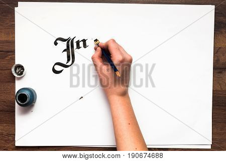 Calligraphy lettering. Artist workplace top view. Unrecognizable painter's hand drawn word inspire with ink on white paper background. Drawing lessons, art school, creativity concept
