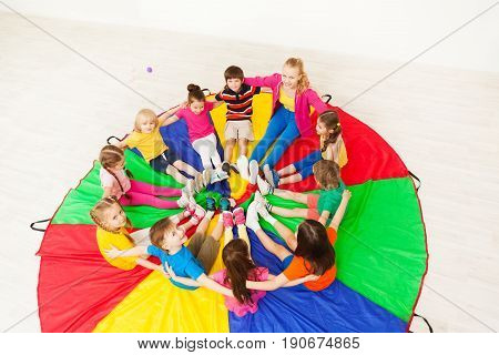 Top view portrait of nursery teacher and happy children sitting on rainbow parachute, playing circle games in kindergarten