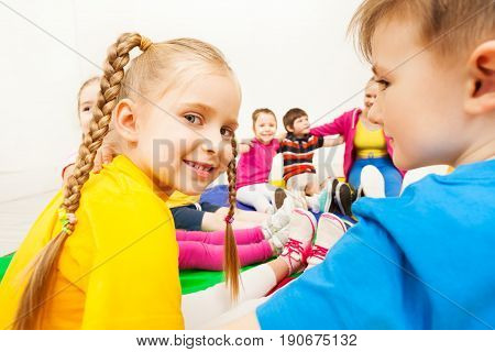 Close-up portrait of blond six years old girl sitting in a circle with friends at school gym