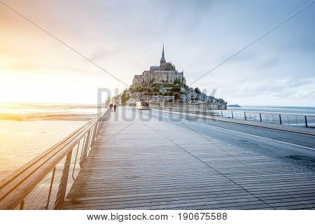 Sunset view on the famous Mont Saint Michel abbey with bridge during the tide in France