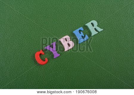 CYBER word on green background composed from colorful abc alphabet block wooden letters, copy space for ad text. Learning english concept