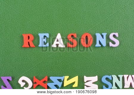 REASONS word on green background composed from colorful abc alphabet block wooden letters, copy space for ad text. Learning english concept