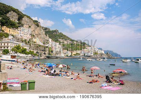 Amalfi Italy - September 1 2016: People sunbath on the picturesque beach of Amalfi town