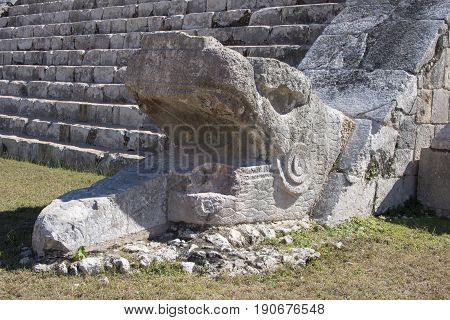 Closeup of stone serpent head sculpture at bottom of rock stairway of El Castillo pyramid on sunny day at Chichen Itza in Yucatan Mexico