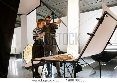 Creative team discussing shoot composition. Photographer taking work with assistant in studio interior. Photoshoot backstage, teamwork, brainstorming concept