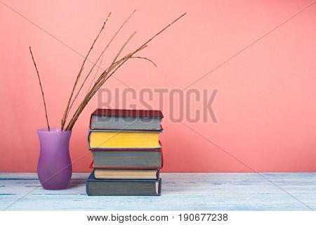 Book stacking. Open book, hardback books on wooden table and red background. Back to school. Copy space for text