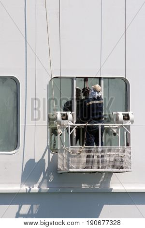 Man in the hanging platform cleaning windows of big passenger ship