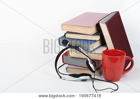 Open book, hardback colorful books on wooden table, white background. Back to school. Headphones, cup. Copy space for text. Education business concept