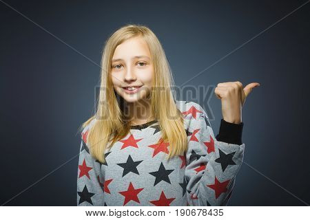 little girl pointing by finger at side and smiling at camera isolated on Gray.