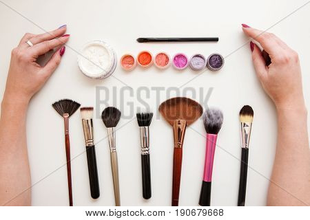 Makeup artist set. Brushes, powder, pigments and woman's hands on white background. Professional tools and eyeshadows for eye visage.