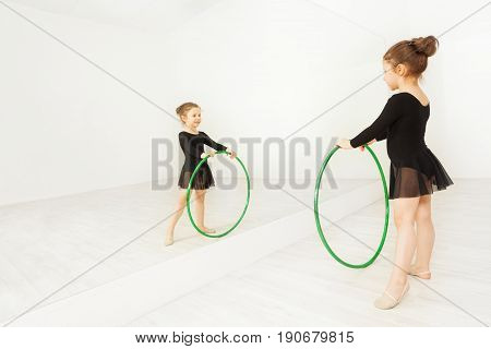 Reflection of five years old girl in black dancewear practicing gymnastic with hula hoop in well lit dance hall