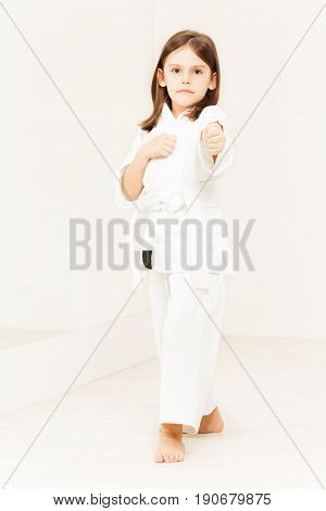 Full length portrait of karate girl wearing white kimono standing in attack stance in gym