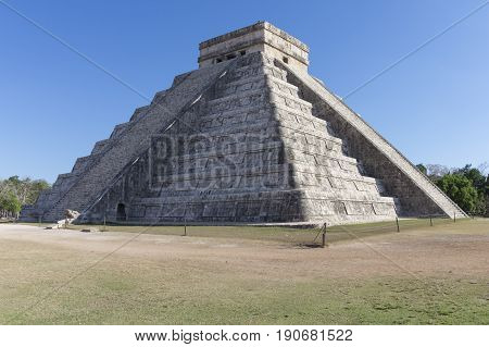 Famous El Castillo Temple of Kukulkan at Maya ruins of Chichen Itza with shadow of serpent along staircase under clear blue sky