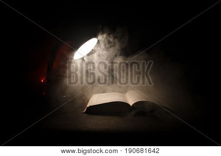 Open Book Near Glowing Table Lamp On Dark Background, Lamp And Opened Book With Smoke On Background.