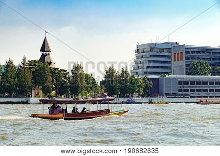 Bangkok, Thailand - December 22, 2015: People travelling by boat in Chao Phraya river overlooking the modern Bangkok with skyscrapers and bridge, Thailand
