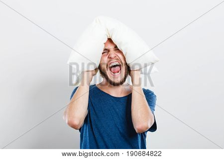 Angry Man Closing Ears With Pillow