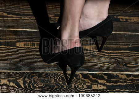 black fashionable shoes on feet of glamour woman rubbed leg on wooden floor background beauty and fashion skincare