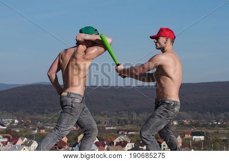 conflict. strong athletes or muscular men with naked athletic torsos in green and red caps and jeans fighting with baseball bat on blue sky on mountain landscape. Conflict and competition. Power success