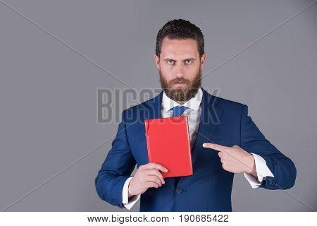 notebook red book in hand of serious man or businessman in blue outfit on grey background copy space business saving book