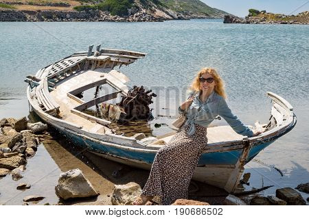 Blonde girl on the shipwreck in the coastline