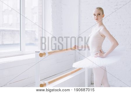 Young attractive ballerina standing at bar in ballet class in front of the camera in a ready position and looking near. She is really serious and concentrated
