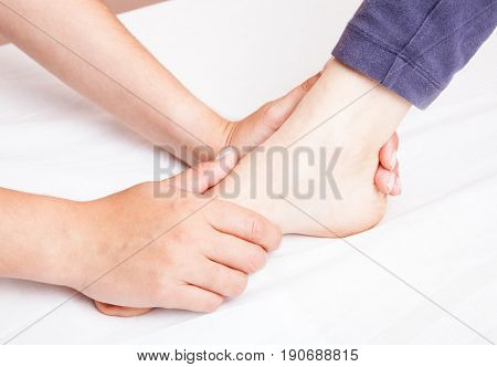 Young woman's foot joint being manipulated by an osteopath - an alternative medicine treatment