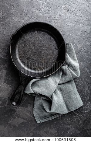 Empty cast iron frying pan on dark grey culinary background view from above