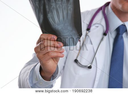 Doctor with stethoscope in blue uniform holding X-rays.