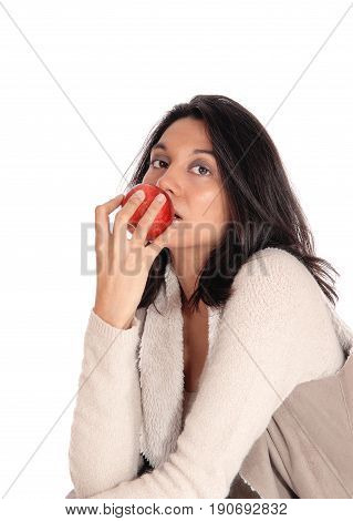 A beautiful young Hispanic woman eating a red apple looking into the camera isolated for white background.