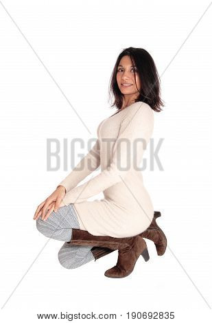 A gorgeous happy Hispanic woman in a knitted dress and boots kneeling on the floor isolated for white background.