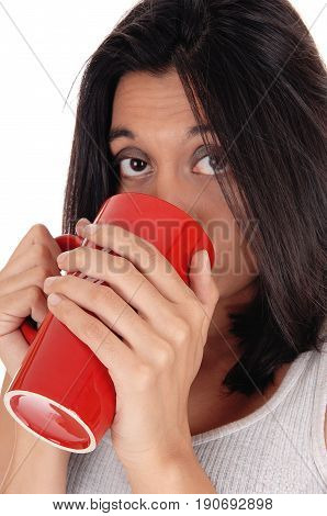 A happy young woman in a white t-shirt holding a red coffee mug on her mouth isolated for white background.