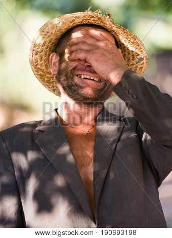 Lubovka - August 14: Ivan Unshaven pose before the camera in a tattered straw hat and jacket his face is closed by hand on August 14 2006 in Lyubovka village Kharkov region Ukraine