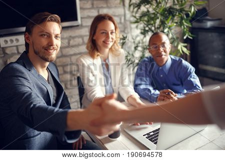 Welcome aboard! businessman shaking hands - you got the job in the team