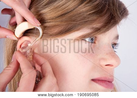Close up of a young girl's head and the audiologist's hands inserting hearing aid into ear
