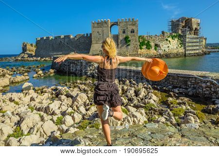 Happy tourist vacation woman with sun hat in the air enjoying on islet of Bourtzi. Methoni Venetian Fortress, a medieval fortification, Peloponnese, Greece. Happiness travel holidays lifestyle concept