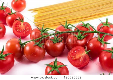 red tomatoes on white.raw pasta backround. Italian food and cooking