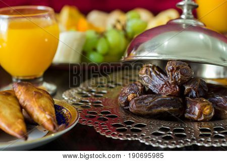 Dried date palm fruits fresh orange juice samosa snack and blurred fruit background concept iftar in the holy month Ramadan. Selective focus