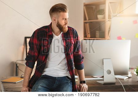 Young male architect working indoors thinking concerned